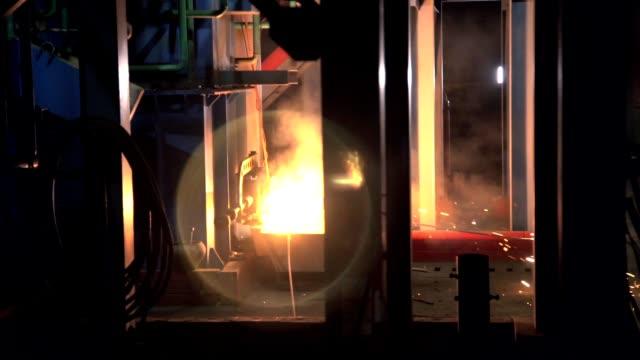 vídeos de stock e filmes b-roll de molten metal pours into container with flame sparkles - formato bruto