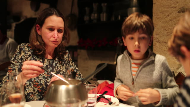 mom and child eating fondue for supper, candid authentic scene of family eating traditional swiss cuisine, fondue - pietanza cotta in tavola video stock e b–roll