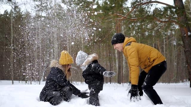 stockvideo's en b-roll-footage met moeder en vader gooien een sneeuw waardoor een sneeuwval voor hun zoon in slow motion. - family winter holiday