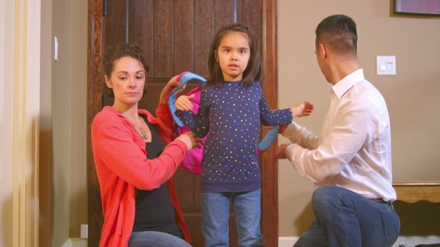 Mom and dad help girl get ready for school video