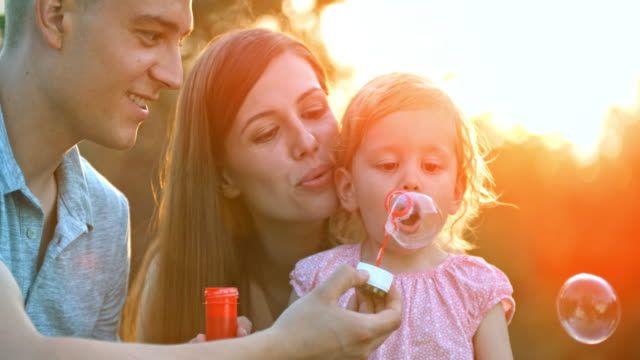 slo mo mamma och pappa att hjälpa lilla småbarn dotter blåsa bubblor vid solnedgången - enbarnsfamilj bildbanksvideor och videomaterial från bakom kulisserna