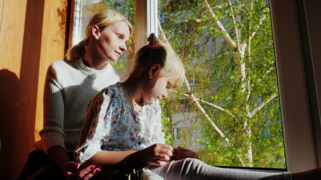 Mom and daughter are 6 years old sitting on the windowsill, looking out the window. Outside the window is spring, green leaves in the trees, the sun is shining. Concept - to wait for someone, to dream video