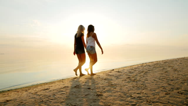 Mom and daughter are a teenager on the beach at sunset. Back view video