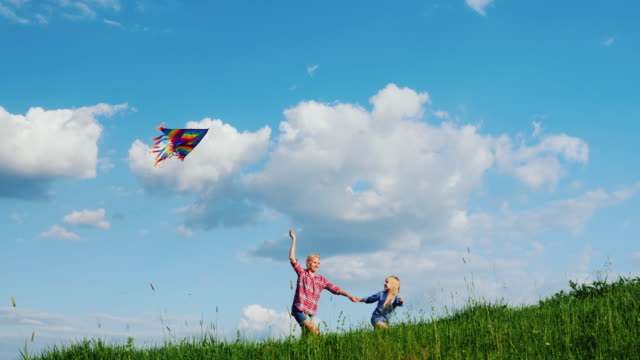 Mom and daughter are playing with a kite. Run along the slope of a large green hill video