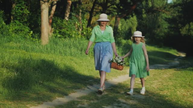 ママと娘は、野生の花のバスケットを運ぶ森の中のパスに沿って歩いています。子供を持つ幸せな親 ビデオ