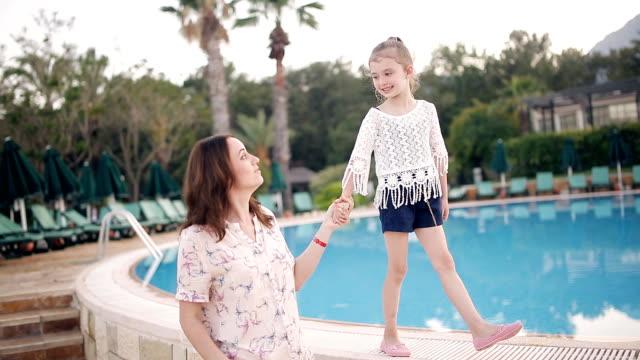 ママと娘がプールサイドで夕方には歩いています。 ビデオ