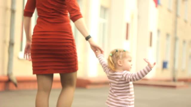 ママと娘は公園で歩いています。 ビデオ