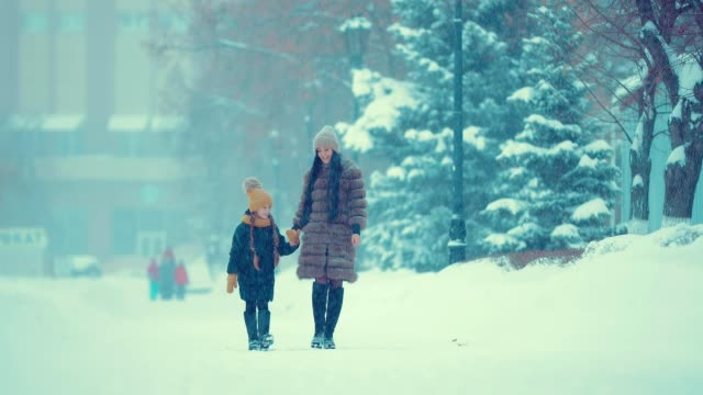 Mom and daughter are walking in the snow. They are talking and happy.