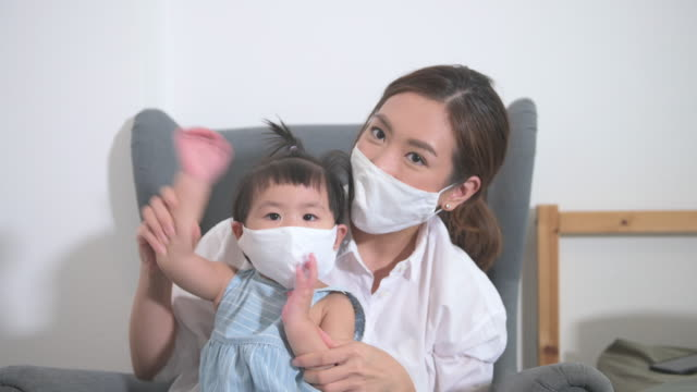 vídeos de stock e filmes b-roll de mom and daughter are wearing protective mask for protecting  from coronavirus infection , safety in home , covid-19 protection , healthy at home concept - vacina da gripe