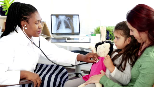 Mom and daughter at the doctor Mom sits with her little sick girl on her lap. An African female doctor checks the little girls doll's heartbeat with a stethoscope. Doctor gives her  a thumbs up., trying to cheer the sick child up. doll stock videos & royalty-free footage