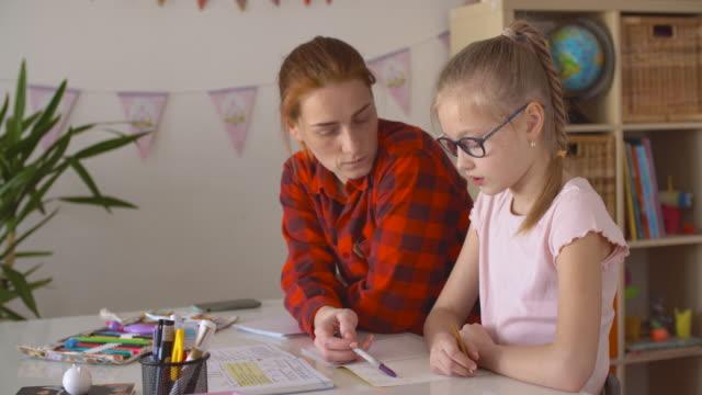 stockvideo's en b-roll-footage met mamma en dochter die thuiswerk samen doen - lagere schoolleeftijd