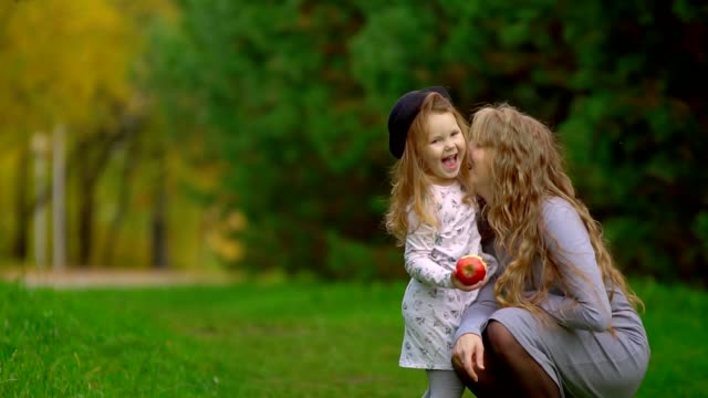 mom and daughter eating an Apple mom and daughter eating an Apple in the Park russian ethnicity stock videos & royalty-free footage