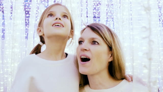 Mom and daughter in fantasy lights at Christmas time