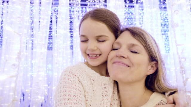 Mom and daughter in fantasy lights at Christmas.