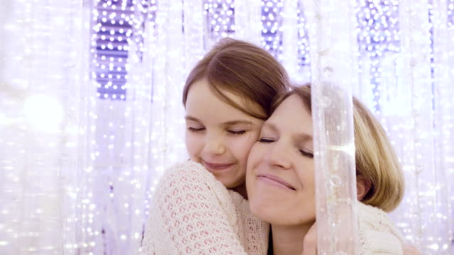 Mom and daughter in fantasy lights at Christmas