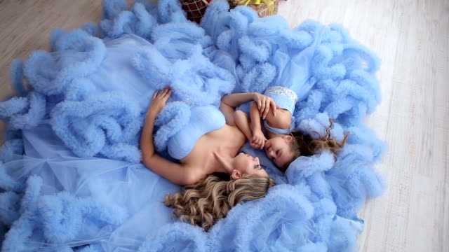 Mom and daughter in fluffy dresses in the Studio. Beautiful mother and her daughter dressed in the same blue fluffy dresses, they lie on the floor and posing for a photographer. princess stock videos & royalty-free footage