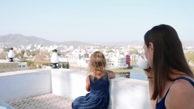 Mom and daughter on balcony are enjoying beautiful views of city and mountains