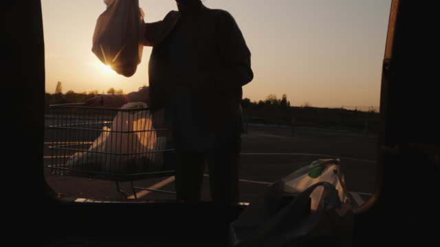 Mom and daughter put shopping from the supermarket in the trunk of the car video
