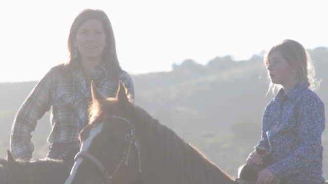 mom and daughter ranchers riding in the evening light - ranch video stock e b–roll