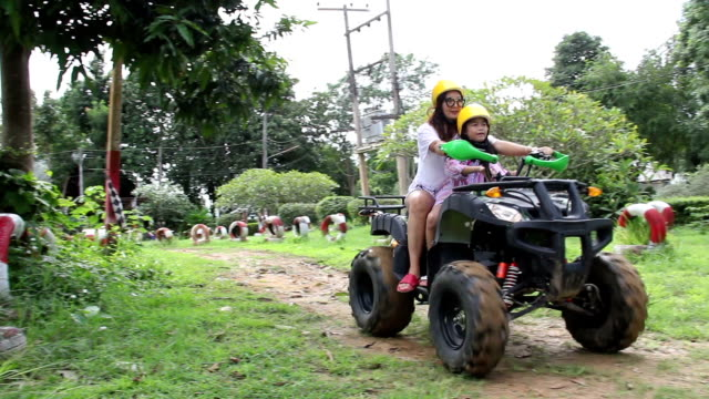 Mom and daughter ride ATV in soil race by relax time video