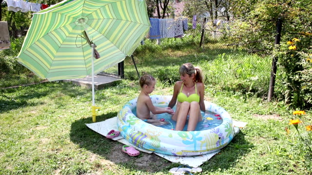vídeos de stock e filmes b-roll de mom and daughter swimming in an inflatable pool - stock video - brinquedos na piscina