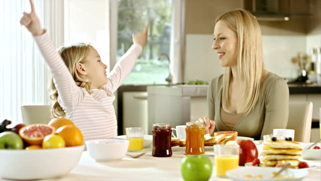 Mom and daughter talk at breakfast table video