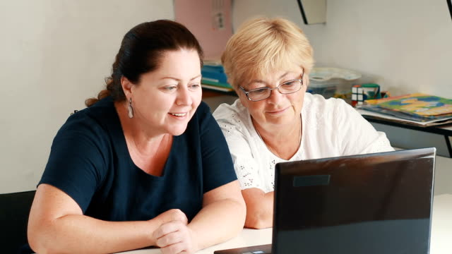 Mom and daughter talking through skype on laptop video