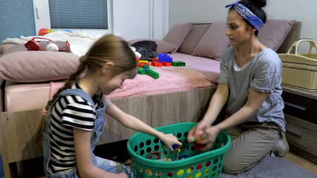 Mom and daughter to tidy up Child scattered toys - vídeo