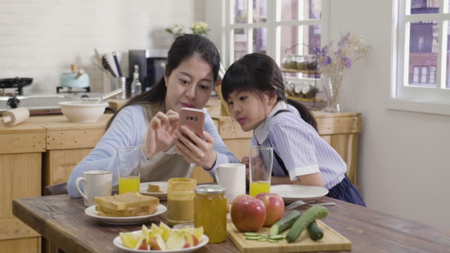 mom and daughter using smartphone in kitchen - stay at home parent stock videos & royalty-free footage