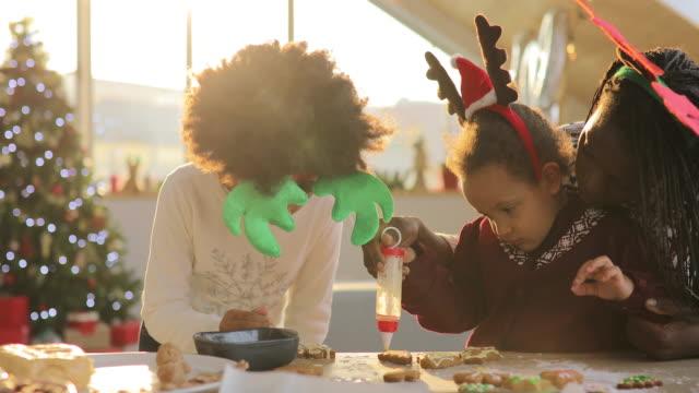 vídeos y material grabado en eventos de stock de madre e hijas decorando galletas - galleta dulces