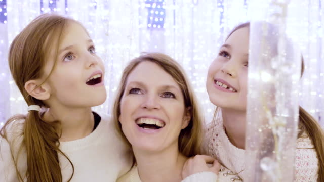 Mom and daughters in fantasy lights at Christmas