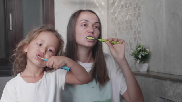 vídeos de stock e filmes b-roll de mom and her cute little daughter is brushing teeth with toothbrushes together. - escovar