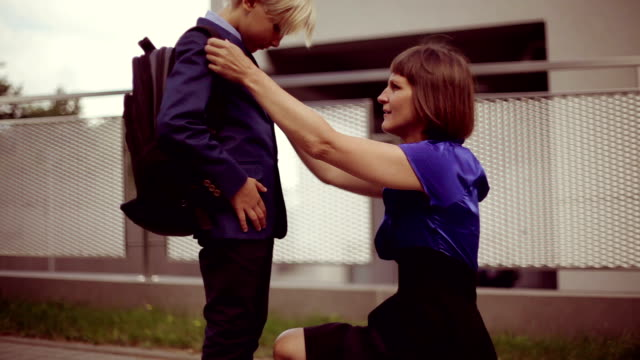 mom and her son (8-9) on goodbye at school fence - schools stock videos & royalty-free footage