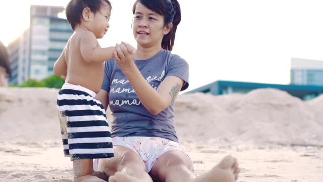 Mom and her son relaxing on the beach. video