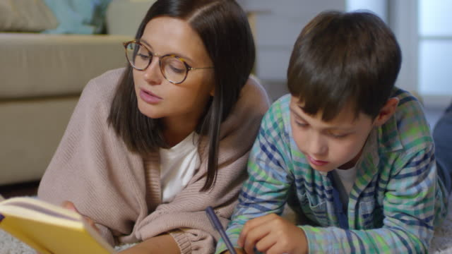 mom and kid doing homework together on floor in living room - scolaro video stock e b–roll