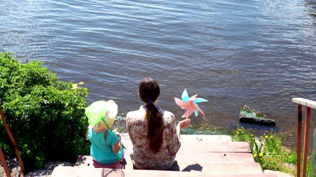 mamma och lilla dotter sitter på bryggan vid sjön. - flod vatten brygga bildbanksvideor och videomaterial från bakom kulisserna