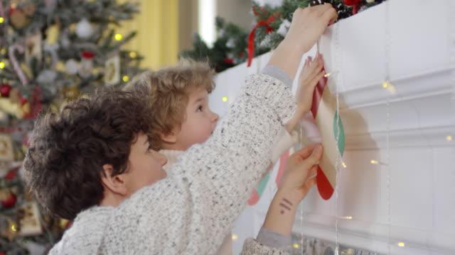 mama und kleiner sohn dekorieren zu hause für weihnachten - weihnachtsstrumpf stock-videos und b-roll-filmmaterial