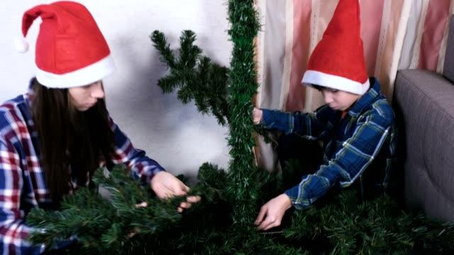 媽媽和在聖誕帽的媽媽和兒子在家裡安裝聖誕樹。 - 人造的 個影片檔及 b 捲影像