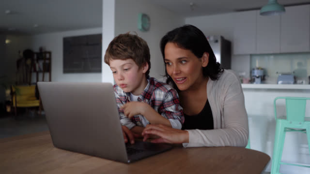 Mom and son looking for something online on laptop while mother explains and points at the screen