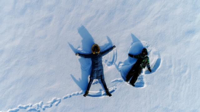 stockvideo's en b-roll-footage met moeder en zoon maken sneeuw engelen samen. camera langzaam stijgen. luchtfoto beeldmateriaal. - alleenstaande moeder