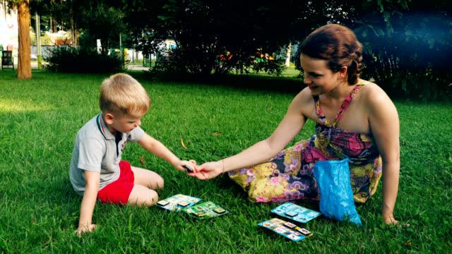 Madre e hijo jugando bingo en la hierba en el parque. - vídeo