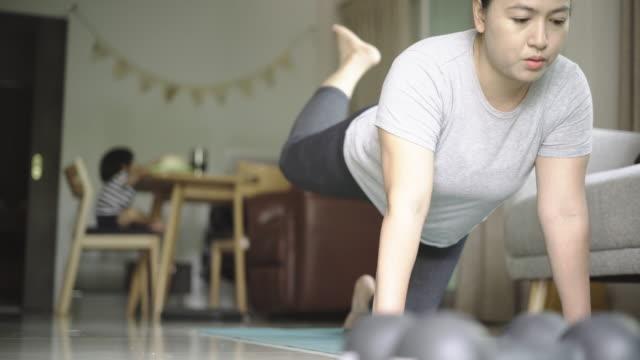 vídeos de stock e filmes b-roll de mom and son relax exercise at home - treino em casa