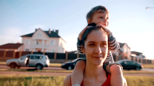Mom and son spend time together. Cute little boy sits on his moms shoulders, she smiles happily. Sun shines. Slow mo video