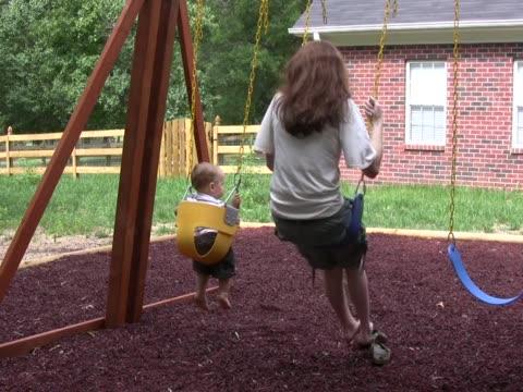 mom and son swing 2 pal - i̇nsan sırtı stok videoları ve detay görüntü çekimi