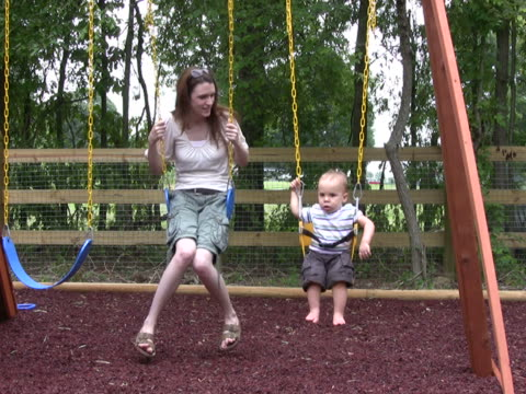 Mom and Son Swing NTSC Mom and Son play on swing. outdoor play equipment stock videos & royalty-free footage