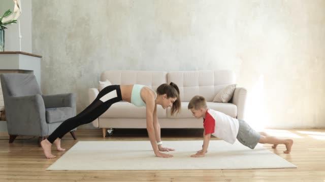 mamma och son tränar tillsammans i plankträning hemma ger fem varandra - hemmaträning bildbanksvideor och videomaterial från bakom kulisserna
