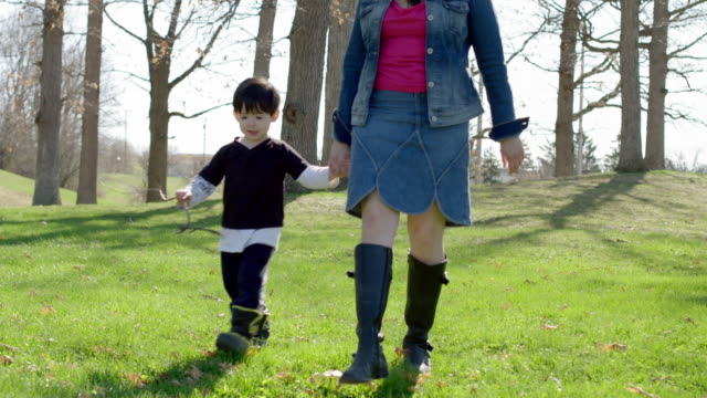 Mom and son walk towards viewer while holding hands video