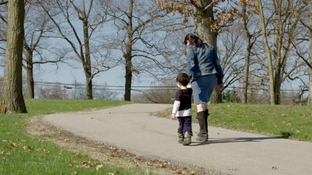 Mom and son walking on path through park video