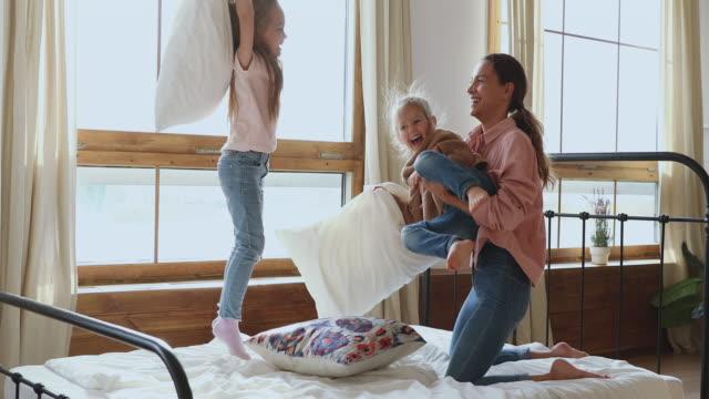 mamma och två söta döttrar spelar kudde slåss i sängen - cosy pillows mother child bildbanksvideor och videomaterial från bakom kulisserna