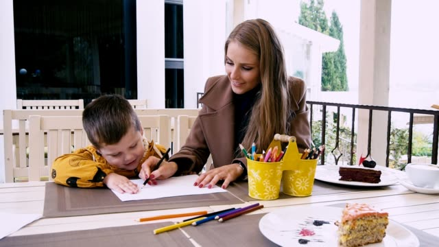 mom and young boy draw with crayons at the table mom and young boy draw with crayons at the table 1 playroom stock videos & royalty-free footage